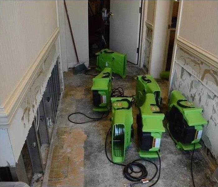 Office hallway with water damaged flooring and some drywall removed and SERVPRO drying equipment standing in the hallway