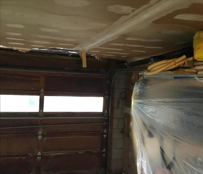 Damaged interior look of garage door and unfinished sheetrock ceiling, and plastic sheeting to protect the items on the shelv