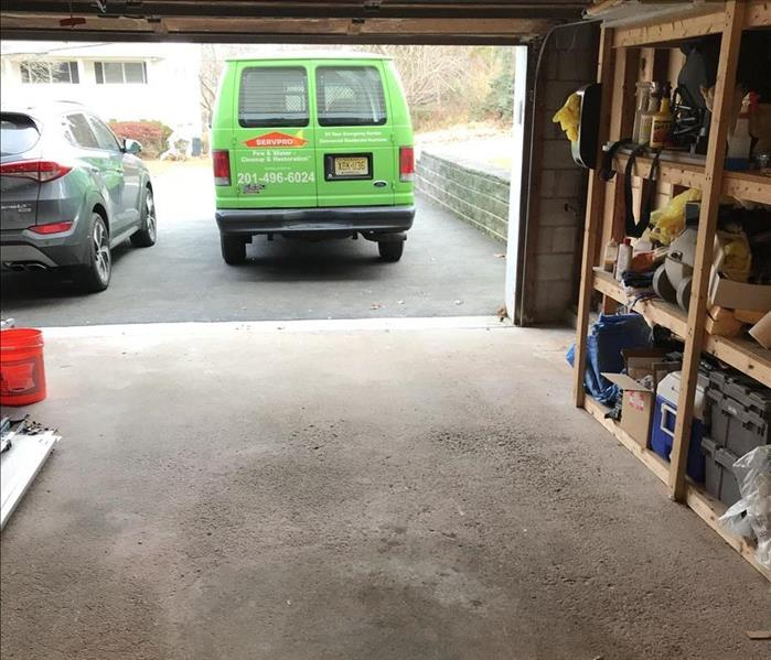 Same view, no garage door with a SERVPRO van in the driveway, neat and clean, with exposed building elements